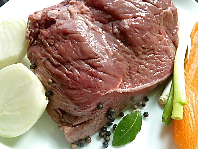 Das Fleisch mit Gemüse und Gewürzen langsam kochen